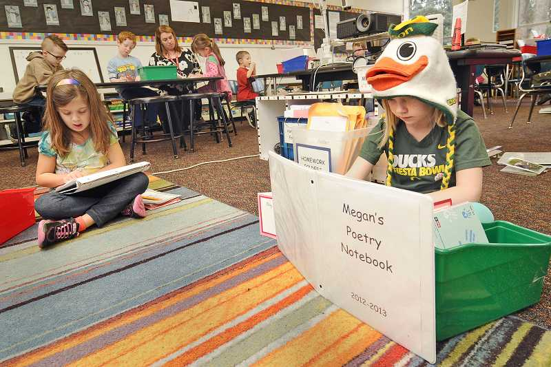 by: TIDINGS PHOTO: VERN UYETAKE - Megan Strobbe, right, and Madeline Noland read from their poetry notebooks in their kindergarten class at Bolton Primary School.