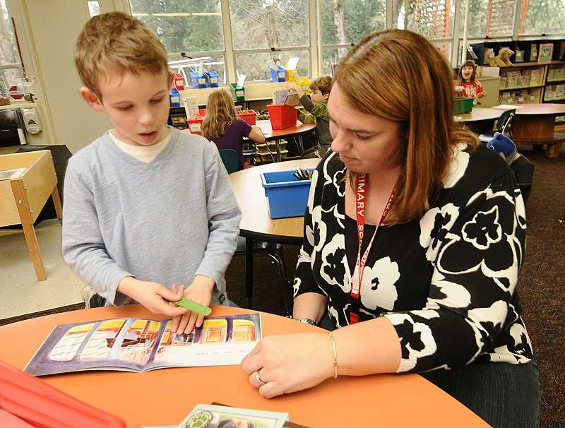 by: TIDINGS PHOTO: VERN UYETAKE - Bolton Primary School kindergarten teacher Alicia Nelson helps Zachary Welch with his reading.