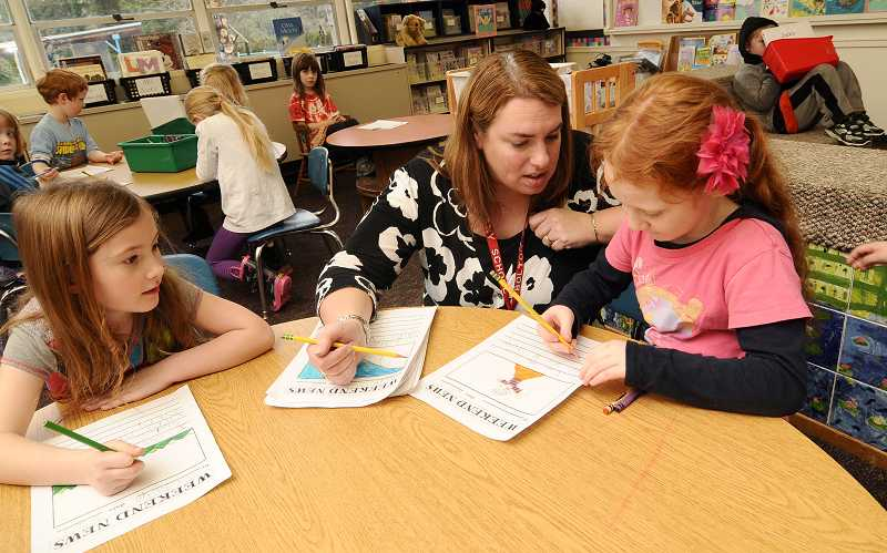 by: TIDINGS PHOTO: VERN UYETAKE - Bolton Primary School kindergarten teacher Alicia Nelson works with Madalyn Hersh, left, and Zoey Kramer.