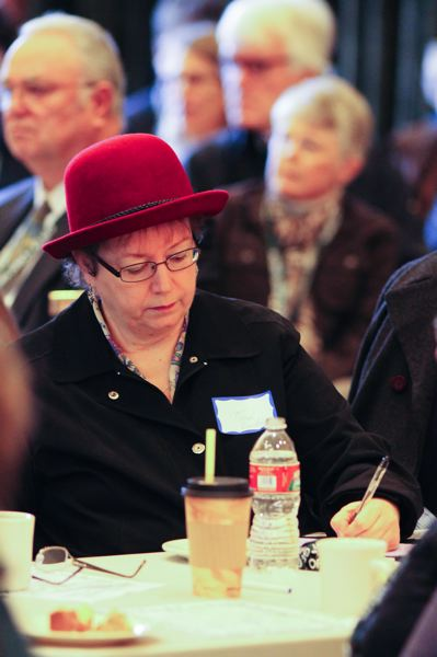 by: NEWS-TIMES PHOTO: JOHN SCHRAG - Forest Grove resident Terri Erskine jots down some notes about the effects of global climate change on local agricultural crops at Saturday's Annual Town Meeting.