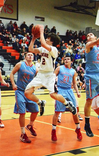 by: JOHN BREWINGTON - Scappoose's Chris Tinning drives to the basket during last Tuesday's win over Seaside. Tinning has become one of the Tribe's top scorers.