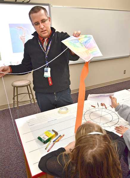 by: REVIEW PHOTOS: VERN UYETAKE - J.R. Pollnow, outreach coordinator for Evergreen Aviation and Space Museum, discusses how kites are lifted in the air.