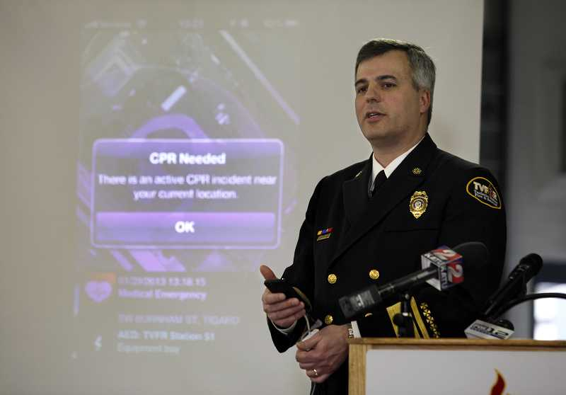 by: TIMES PHOTO: JONATHAN HOUSE - Tualatin Valley Fire & Rescue Fire Chief Mike Duyck demonstrates the district's new PulsePoint app for smartphones that alerts bystanders when someone nearby needs CPR.