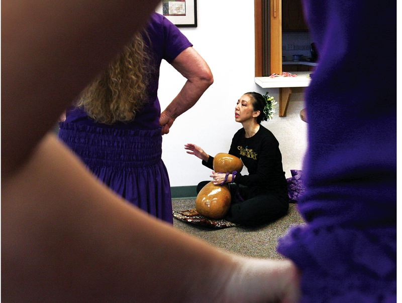 by: JIM CLARK/PAMPLIN MEDIA GROUP - Lisa Chang accompanies her hula students on percussion during a lesson for her 55-and-older  class in Aloha. Chang's classes include not just hula but Hawaiian culture and language, songs and dances for people of all ages.