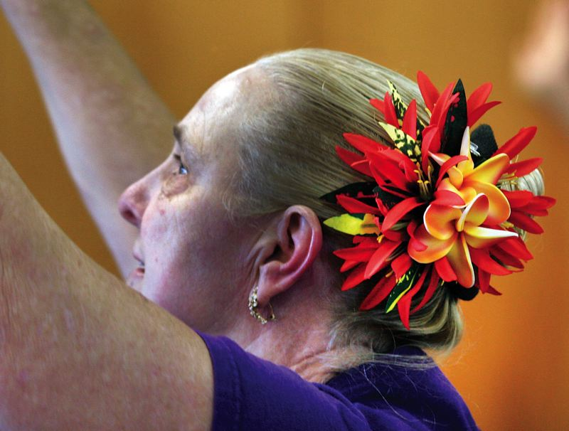 by: JIM CLARK/PAMPLIN MEDIA GROUP - Barbara Archer wears a flower hair ornament as part of her class uniform, which also includes a purple T-shirt and purple skirt. Purple is the color of Hawaii, says instructor Lisa Chang.