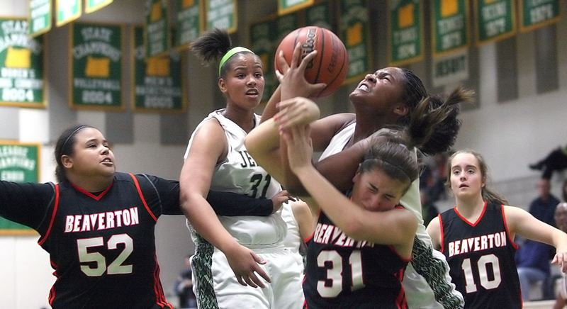 by: MILES VANCE - MUSCLE UP - Jesuit's Alzena Henry and Beaverton's Gigi Stoll wrestle for control of a reound during the Beavers' 47-33 win over the Crusaders at Jesuit High School on Friday.