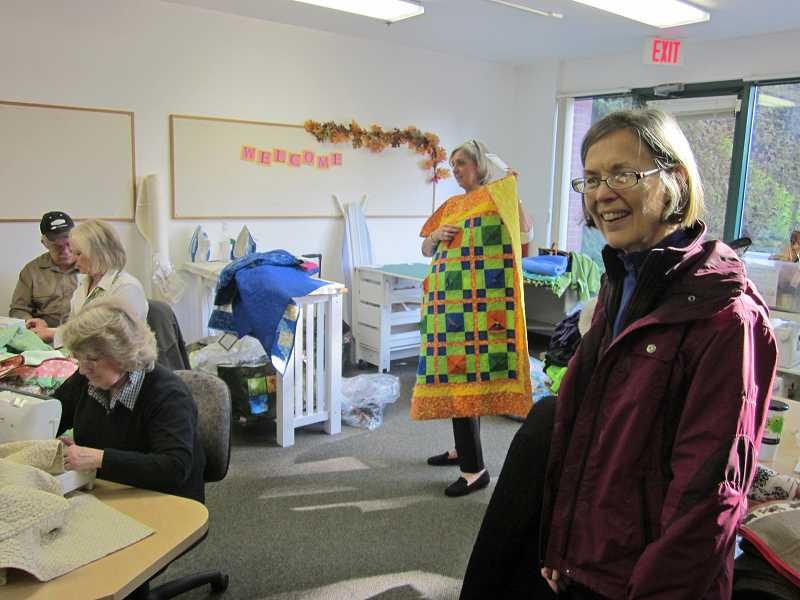 by: BARBARA SHERMAN - BUSY BEES - Above) Karen Oakley (right), a volunteer with the Oregon Department of Human Services, stops by the Jan. 17 meeting of the Portland/Vancouver chapter of Project Linus to gather up blankets to give to children picked up in crisis situations while Lou Pottratz, Constance Dorreman, Sue Ward and Martha Craven keep working.