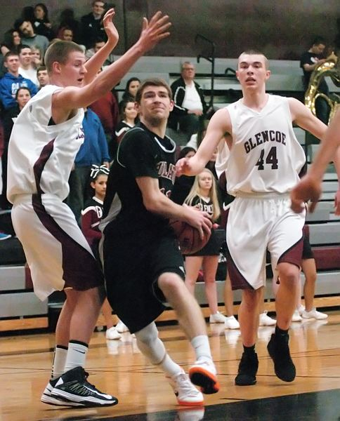 by: DAN BROOD - SPLIT THE ZONE -- Tualatin High School senior Scott Allred drives between a pair of Glencoe defenders in Friday's game. Allred had eight steals, including five in the first two minutes, in the 102-67 victory.