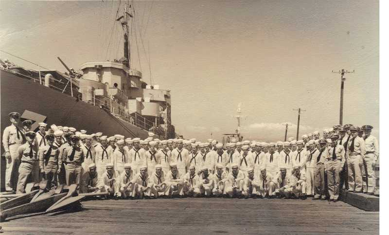 by: COURTESY OF BRUCE CLARK - CREW PORTRAIT - The crew of the U.S. Navys USS Albuquerque stands on a dock beside the ship in the Hong Kong Harbor during the Korean War.