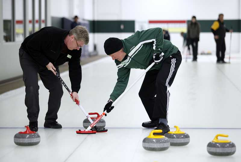 by: TIMES PHOTO: JONATHAN HOUSE - Bruce Irvin, left, and Patton Echols sweep ahead of stone at the Evergreen Curling Club.