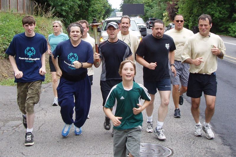 by: PHOTO COURTESY: CCSO - Clackamas County Sheriff Craig Roberts (right) runs in a Special Olympics Torch Run event with CCSO employees and other participants.