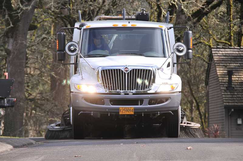 by: VERN UYETAKE - Lake Oswego's heavy-duty street-sweeping machines pick up leaves and debris on the city's streets, a service that prevents flooding during rainstorms and helps keeps waterways clean.