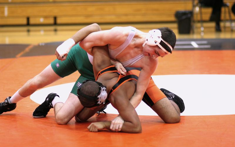 by: NEWS PHOTO: LOREN NIBBE - Sophomore Stone Rathburn tangles with a Molalla wrestler during a Jan. 30 away meet.