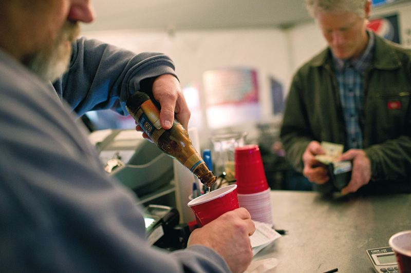 by: TRIBUNE PHOTO: CHRISTOPHER ONSTOTT -  Jim Ginotti pours a beer into a red cup inside the Cartlandia beer garden for a customer. Despite initial concerns from the OLCC and police, the beer garden has been a mellow place.