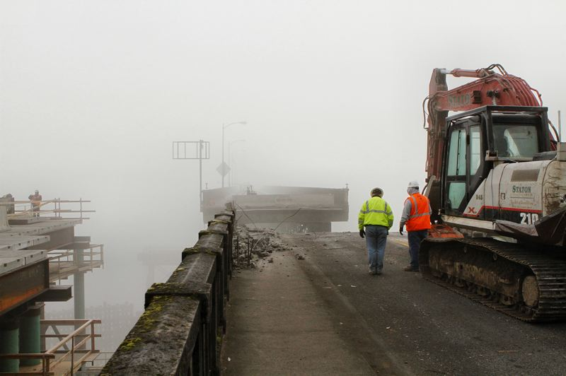 by: DAVID F. ASHTON - Workers watch as the Sellwood Bridge truss starts its journey, looking like a ship pulling away from its dock, in the thick morning fog.