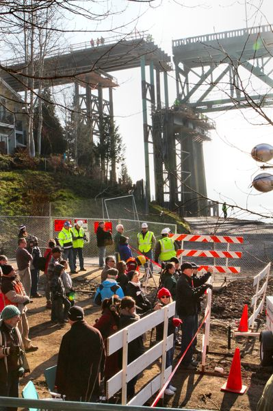 by: DAVID F. ASHTON - At the end of S.E. Spokane Street, people gather to watch the Sellwood Bridge truss move north. The disconnection of the old east-end ramp to permit the truss to move north is clearly visible overhead.