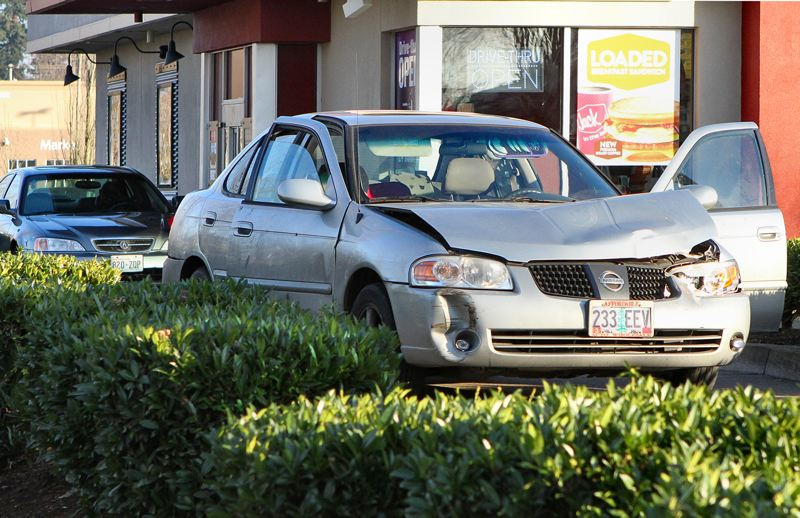 by: DAVID F. ASHTON - Fresh bullet holes are clearly visible on the opened door of this Nissan automobile.
