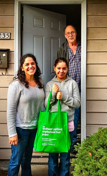 by: PETER KORCHNAK - Woodstock resident Dawn Johnston, and her daughter Emma, pick up a food donation from neighbor Randy Eisenbeisz last December 8th.