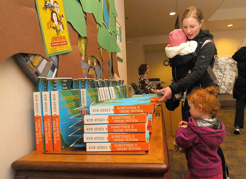 by: VERN UYETAKE - Carlee Kelly with her daughters, Elin and Madelin, picks up her copy of 'Sometimes a Great Notion' Friday at the West Linn Library.