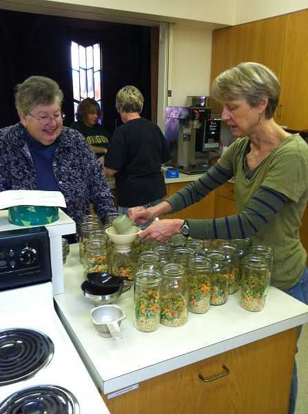 by:  KIRSTEN WYATT - Janet Enger, left, and Gretchen Dumestre prepare soup dinners that were delivered to West Linn Neighbors Helping Neighbors families.
