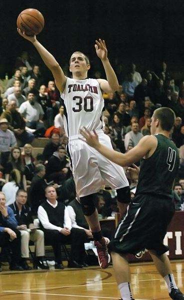 by: DAN BROOD - FLOATING -- Tualatin senior C.J. Michael looks to go past Tigard's Will Schaer on his way to the basket in Friday,s game. Michael scored 18 points to lead the Timberwolves.