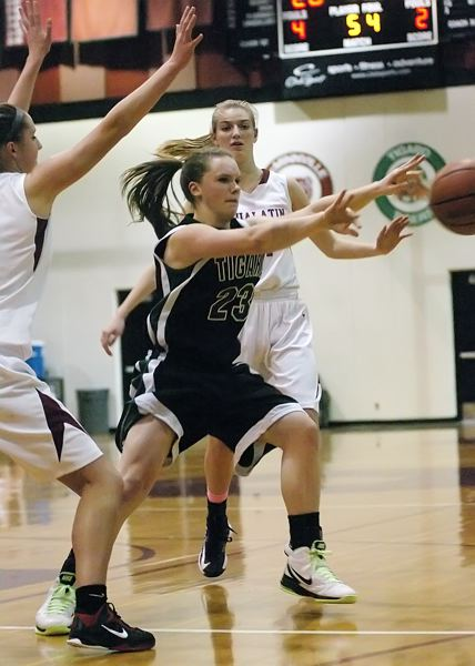 by: DAN BROOD - PASS FROM THE POST -- Tigard senior Megan Risinger passes the ball to the outside during Friday's game. Risinger scored 18 points in the Tigers' 46-44 overtime victory.