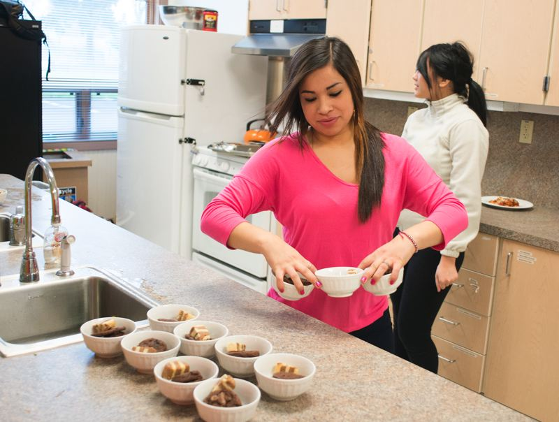 by: TRIBUNE PHOTO: CHASE ALLGOOD - Liz Rodriguez and Irene Chhvoey prepare deserts for the FEAST lunch.