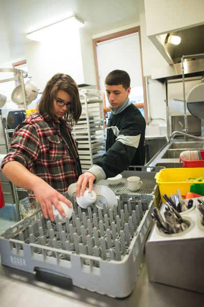 by: TRIBUNE PHOTO: CHASE ALLGOOD - Jordan Neeper and Christian Tovar wash dishes after a recent FEAST luncheon.