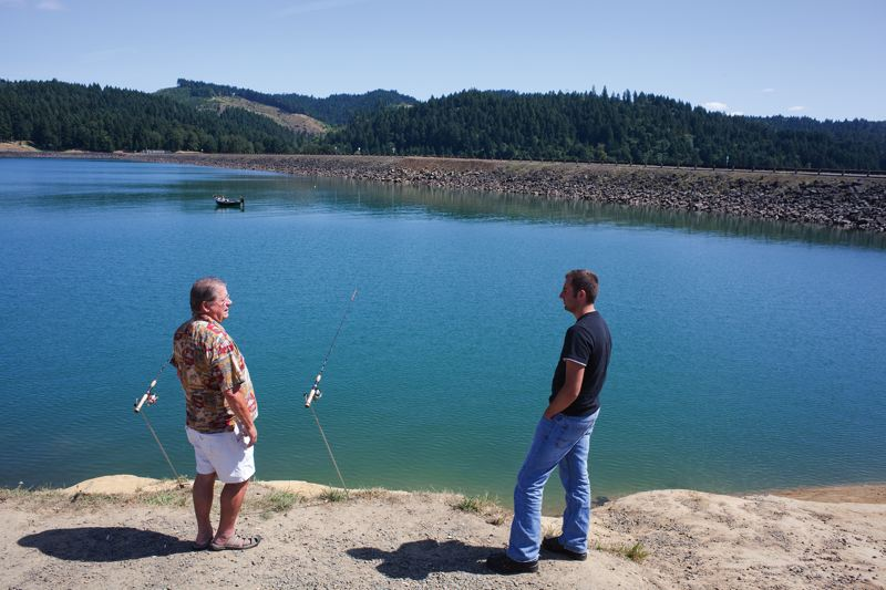 by: TRIBUNE PHOTO: CHASE ALLGOOD - Ed Goettle and Victor Malamura fish next to the dam at Hagg Lake. Raising the dam would increase the capacity of the lake.