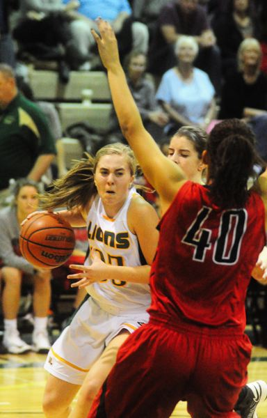 by: MATTHEW SHERMAN - West Linn's Sidney Kolasinski keeps the ball away from a Clackamas defender during a drive to the hoop in Tuesday's game.