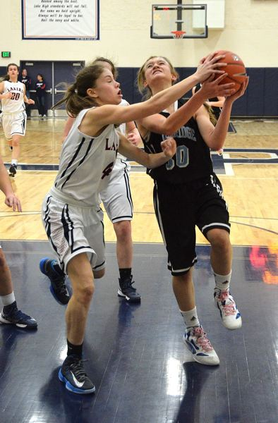 by: VERN UYETAKE - Lakeridge's Natalie Bristol drives against Hannah Plott in last week's victory by the Pacers.