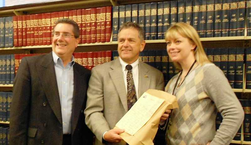 by: SUBMITTED - Larry Peterson holds an unpublished letter written by Ernest Hemingway. Scott Hamersly, left, is president of the CCC Foundation Board and Jennifer Dalglish is from the Law Library.