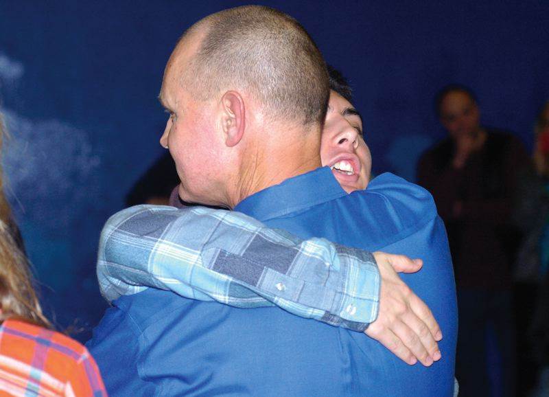by: THE OUTLOOK: DAVID BALL - Barlow High basketball coach Tom Johnson embraces son Jared after Fridays win landed him at milestone 500 for his prep career - the last 26 spent with the Bruins.