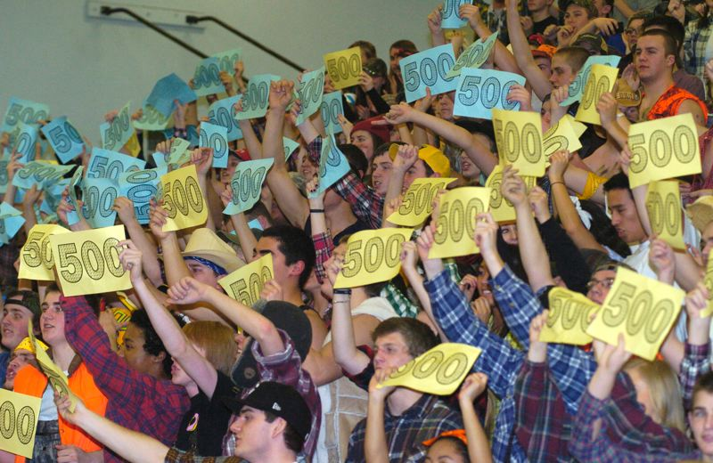 by: THE OUTLOOK: DAVID BALL - The Barlow student section holds up 500 signs to celebrate as the final seconds tick of the clock Friday night.