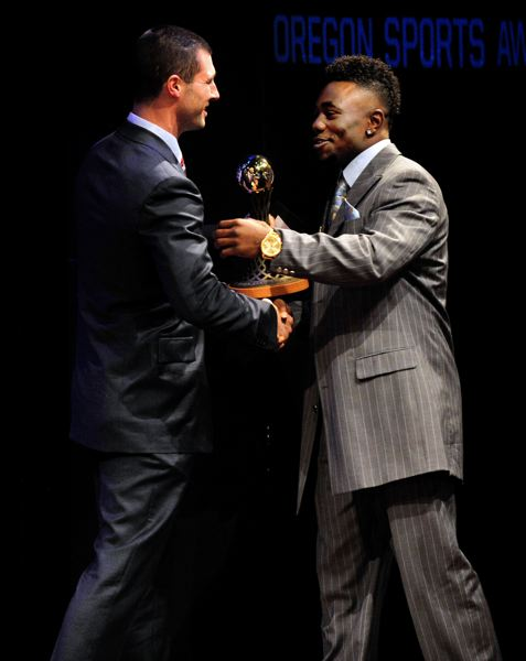by: JOHN LARIVIERE - Kenjon Barner (right), the Oregon Ducks' standout running back, accepts the Bill Hayward Amateur Athlete of the Year Award for men from former UO quarterback Joey Harrington during the Oregon Sports Awards show at Nike on Sunday.