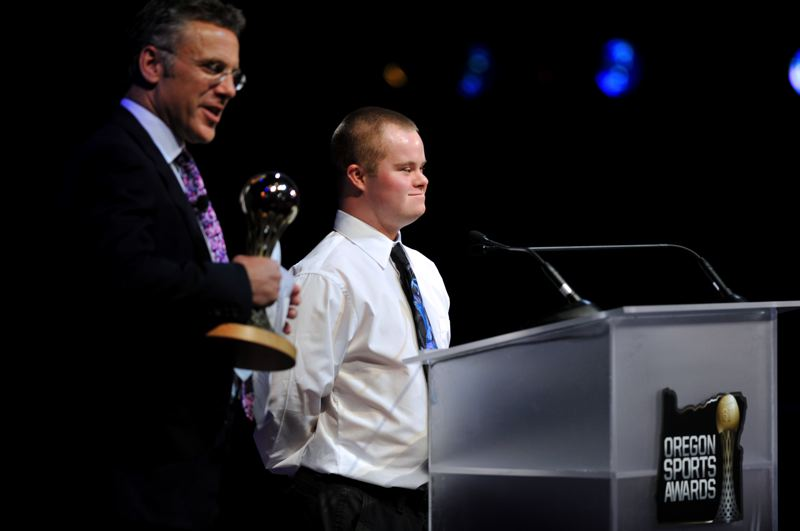by: JOHN LARIVIERE - Dony Knight (right) of Sutherlin High wins the Special Olympics Athlete of the Year Award on Sunday, with the trophy presented to him by ESPN SportsCenter and Oregon Sports Awards host Neil Everett.