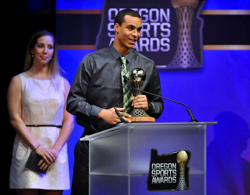 by: JOHN LARIVIERE - Oshay Dunmore, former track and field and football star at Newport High, is honored at the Oregon Sports Awards, with trophy presenter and two-time Olympic individual fencing champion Mariel Zagunis in the background.