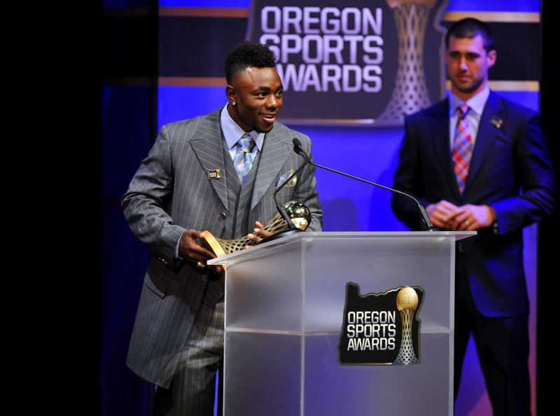 by: JOHN LARIVIERE - Kenjon Barner, who starred at running back for the Oregon Ducks, accepts his trophy as the Bill Hayward Amateur Athlete of the Year for men from 2012, as presenter Joey Harrington looks on at the 61st annual Oregon Sports Awards.
