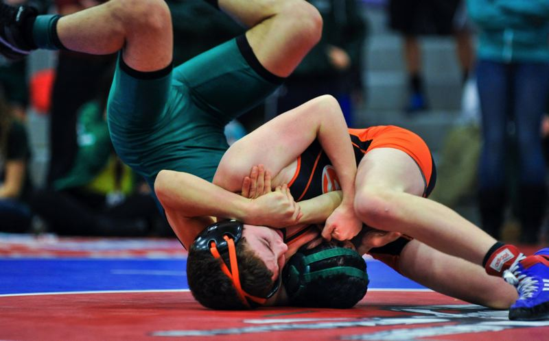 by: JOHN LARIVIERE - Gladstone sophomore Blake McNall takes North Marion junior Adam Vega for a ride in the 113-pound final at Saturdays Tri-Valley Conference District Wrestling Tournament. McNall had little trouble winning the match, defeating Vega by fall in just 1:01.