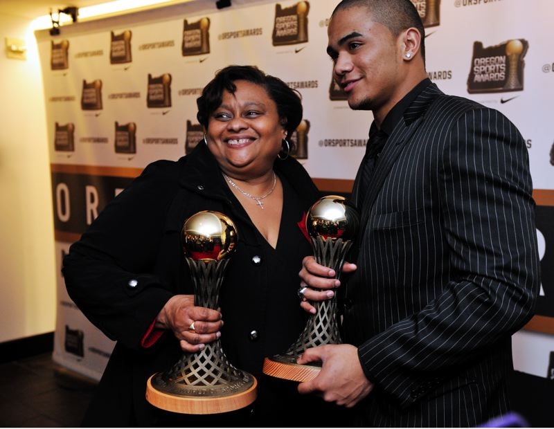 by: JOHN LARIVIERE - Aloha High running back Thomas Tyner captured two trophies at the Oregon Sports Awards on Sunday and celebrates with Tecla Prince, mother of Aloha sprinter Sheldon Prince, who was a finalist for Prep Boys Track and Field Athlete of the Year. Tyner was voted the Johnny Carpenter Prep Athlete of the Year for Class 6A-5A boys and the state Prep Football Player of the Year.