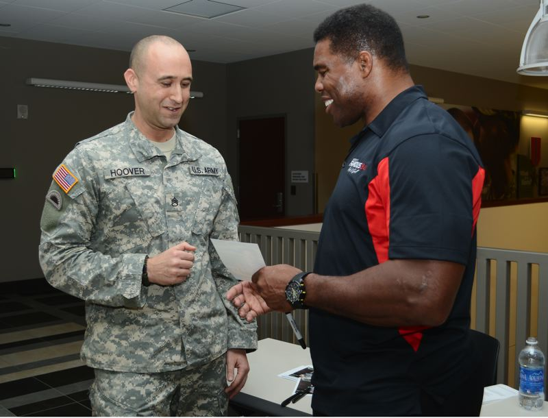 by: PHOTO BY: STAFF SGT. APRIL DAVIS - During the Feb. 6 event, Herschel Walker signs an autograph for Oregon Army National Guard Staff Sgt. Terrence Hoover.