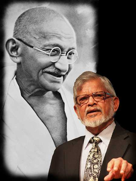by: SUBMITTED - Arun Gandhi stands before a huge photo of his grandfather, Mahatma Gandhi. The grandson has been a tireless crusader in the effort to promote world peace.