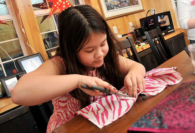 by: VERN UYETAKE - Annika Lo, 9, works on sewing LED lights into a bandana with the PDX Young Makers.