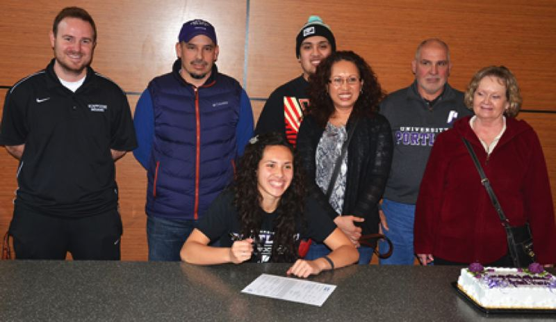 by: JOHN BREWINGTON - Scappoose High soccer phenom Ariel Viera was all smiles, as usual, last Thursday when she signed her letter of intent to play soccer for the University of Portland next fall. Viera has wanted to play for the Pilots since she was little and unofficially committed to them when she was a freshman. UP is a soccer powerhouse, rated as one of the top five programs in the country. The entire Scappoose soccer team and her family turned out to watch. Pictured above is Ariel (with pen and paper), and (from left) Scappoose Coach Chris Dorough, father Dave Viera, brother David Viera, mother Josie Viera, grandfather Dave Viera, and grandmother Linda Viera. Ariel said she will start working out with the team this summer. Practices officially begin in August.