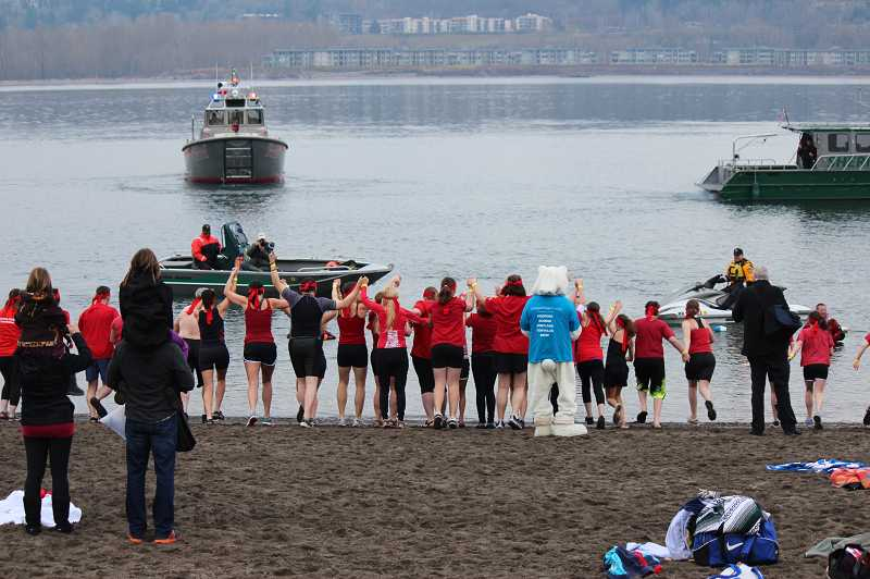 by: SUBMITTED PHOTO - The team jumps into the Columbia River during Saturdays Polar Plunge. The water Saturday morning was 37 degrees, Johansen said.
