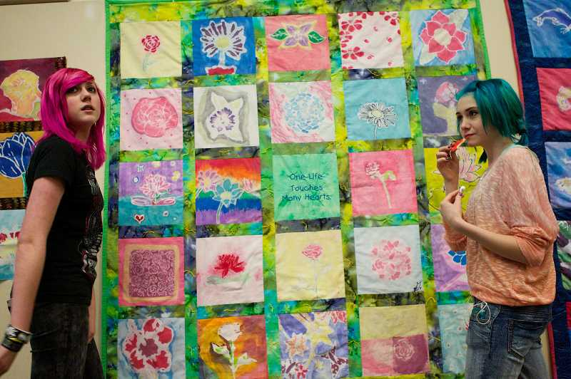 by: TIMES PHOTO: JAIME VALDEZ - Twality Middle School 8th graders Sabrina Blake, left, and Sienna Symonds show off one of two large quilts that will soon be on display in Newtown, Conn.