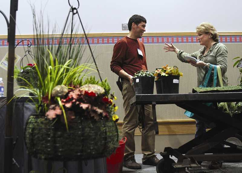 by: TIMES PHOTO: JONATHAN HOUSE  - Jonn Karsseboom, left, of Tualatin's Garden Corner talks with Laura Patton after giving a seminar on hanging basket gardens at the 2013 Yard, Garden and Patio Show. Tens of thousands of people flocked to the outdoor gardening-themed show at the Oregon Convention Center.