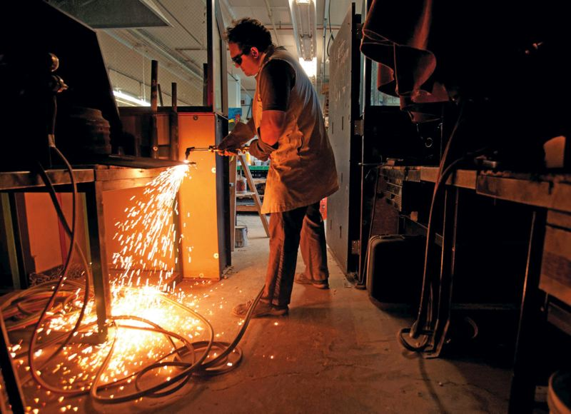 by: TRIBUNE PHOTO: JONATHAN HOUSE  - Madison High School art teacher Joe Rozewski uses a cutting torch to tear through a sheet of metal in his bottom floor art class.
