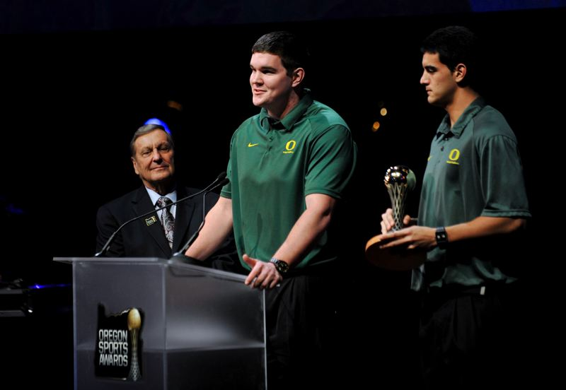 by: JOHN LARIVIERE - Accepting an award for former Oregon Ducks coach Chip Kelly, UO football players Taylor Hart (center) and Marcus Mariota (right) take the Oregon Sports Awards stage alongside presenter and coaching legend Mouse Davis.