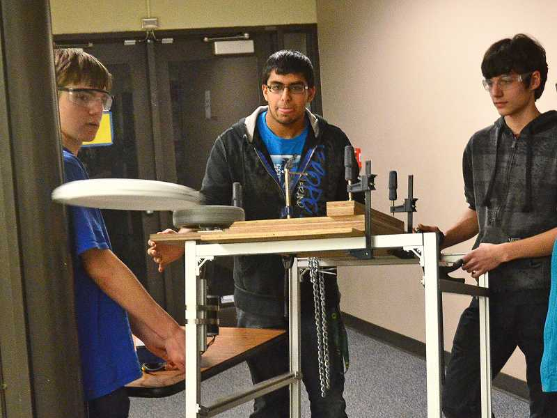 by: REVIEW PHOTOS: VERN UYETAKE - From left, Daniel Ragsdale, Ankit Agarwal and Ethan Russell make refinements to the Frisbee throwing mechanism.